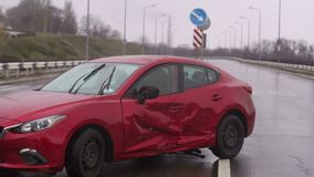 Car accident on the road during the rain. Red damaged car on an empty road.