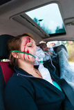 Car accident - Victim in crashed vehicle receiving first aid Stock Photography