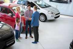 Car agent congratulate the family on buying car. Car agent handshake with his daddy and congratulate the family on buying car royalty free stock photos