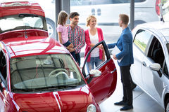Car agent showing vehicle to young family. Smiling car agent showing vehicle to young family, all stand together next to the car in the car dealership saloon royalty free stock images
