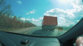 The car is ahead of the truck and the tractor is driving along the road. road slow-motion video view from the cockpit. The car is ahead of the truck and tractor stock footage