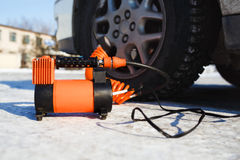 Car air compressor in working position at snow. Self-inflating wheels, automobile tire pressure control. Stock Photos
