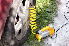 Car air compressor with yellow twisted hose. Checking the tire pressure Stock Photos