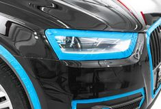 Car in applying blue protective tape before polishing. Buffing and polishing car. Car detailing. Car service. Tools for polishing. Car stock image
