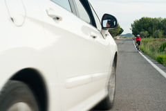 Car approaches cyclist Royalty Free Stock Image