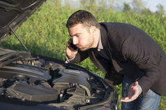 Car assistance. Handsome young man calling for assistance with his car broken down by the roadside Stock Image