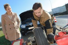 Car assistant worker changing wheel car. Car assistant worker changing the wheel of a car Stock Image