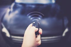 Car Auto Alarm Central Lock. Car Auto Alarm and Remote Central Lock. Car Keys in Driver Hand Sending Signal to the Vehicle Stock Photo