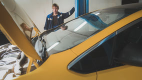 Car in auto service lifting for repairing, mechanics in garage Royalty Free Stock Photography