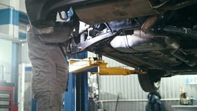 Car auto service - mechanic checks details of car under bottom of vehicle. Close up stock footage