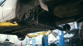 Car auto service - mechanic repairs of the car - works under bottom of vehicle. Close up stock video footage