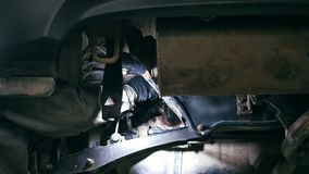 Car auto service - mechanic unscrews detail of car under bottom of vehicle. Close up stock footage