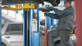 Car auto service working - mechanic under the car. Close up stock footage