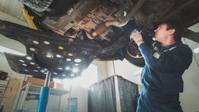 Car automobile service - worker mechanic checks the bottom of car Royalty Free Stock Images