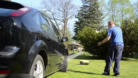Car automobile washing with strong water jet on garden lawn Stock Photos