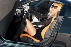 Car and babe. Glamorous blond babe sitting in tuned supercar royalty free stock image