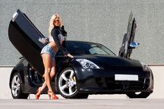 Car and babe. Sexy babe standing in front of tuned supercar
