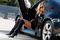 Car & babe. Glamorous blond babe sitting in tuned supercar Stock Photos