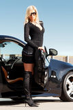 Car & babe. Glamorous blond babe standing near tuned supercar Royalty Free Stock Image