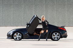 Car & babe. Glamorous blond babe standing near tuned supercar Stock Photography