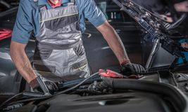 Car Battery and Alternator. Problem. Caucasian Automotive Mechanic Trying to Find Source of the Problem Looking Under Car Hood royalty free stock image
