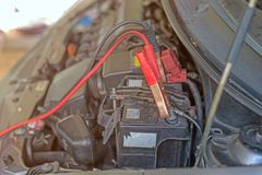 car battery clamped with black and red jumper cable to recharge Stock Photography