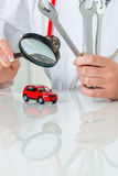Car is being examined by doctor. A model of a car is examined by a doctor. symbolic photo for workshop, service and car buying stock photography