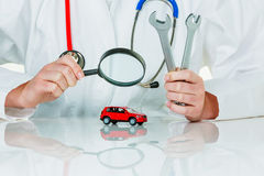 Car is being examined by doctor. A model of a car is examined by a doctor. symbolic photo for workshop, service and car buying stock image