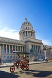 A car-bike with tourists. A car-bike with tourists circle in front of the Capitol of Havana; Cuba Royalty Free Stock Image
