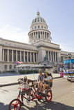 A car-bike with tourists circle in front of the Capitol. In Havana, Cuba. The National Capitol Building was the seat of government in Cuba until the revolution Stock Photos