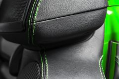 Car black leather interior. Part of leather car seat details with green stitching. Interior of prestige modern car. Comfortable pe. Rforated leather seats. Black stock images