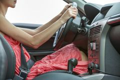 Car black luxurious interior. Profile of young pretty woman in short dress driving a car.  stock photos