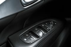 Car black perforated leather interior details of door handle with windows controls and adjustments. Car door handle inside the lux. Ury modern car. Switch button Royalty Free Stock Photography