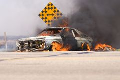 Car blaze. Car in flames at side of road stock photo