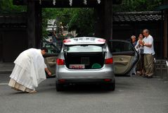 Car blessing. Shinto priest blessing a car with the owner's family watching Stock Image