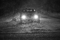 Car in blizzard black and white. A car driving on the road in the aggravated traffic due to strong snowfall Royalty Free Stock Image