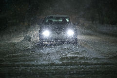 Car in blizzard. A car driving on the road in the aggravated traffic due to strong snowfall Royalty Free Stock Photo