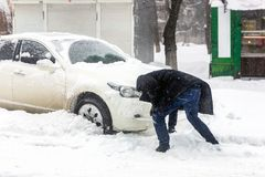 Car blocked with snow drift on city street. Man cleaning vehicle from snow with brush during heavy snowfall, blizzard and storm. W royalty free stock photography