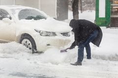 Car blocked with snow drift on city street. Man cleaning vehicle from snow with brush during heavy snowfall, blizzard and storm. Weather forecast in winter stock photography