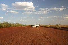 Car blocking the road. Red Australian rural road with a car parked over the road. Tanami road, Northern Territory. Australia Royalty Free Stock Photos