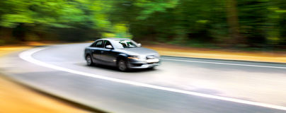 Car in blurred motion on road. Abstract background. Stock Images