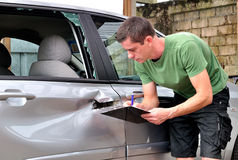 Car body mechanic checking out damage. Stock Photo