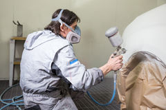 Car body painter spraying paint on bodywork parts Stock Photos