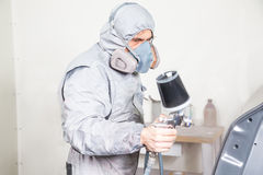 Car body painter spraying paint on bodywork parts stock photography