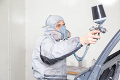 Car body painter spraying paint on bodywork parts stock images