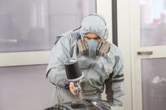 Car body painter spraying paint on bodywork parts stock photos