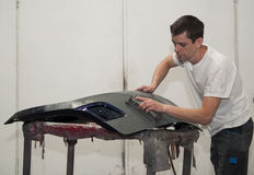 Car body work. Worker repairing car body in a garage Stock Image