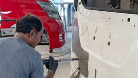 Car body work after the accident by preparing automobile for painting during repair royalty free stock photo
