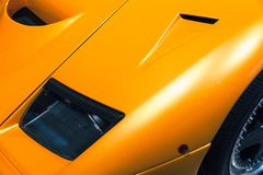 Car bonnet on a luxury yellow roadster. Headlight and car bonnet on a luxury yellow roadster royalty free stock image