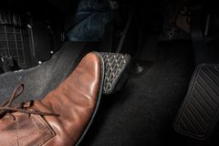 Car brake pedal. Foot pressing the brake pedal of a car Royalty Free Stock Photo